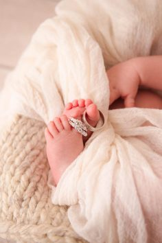 Newborn with wedding rings on toes